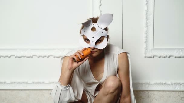 A girl dressed as a rabbit licks and nibble carrots isolated on white. Funny brutal bunny girl. Nibbles a carrot like a hare. Ready for the party. Pretty, trendy woman is wearing bunnies leather mask.