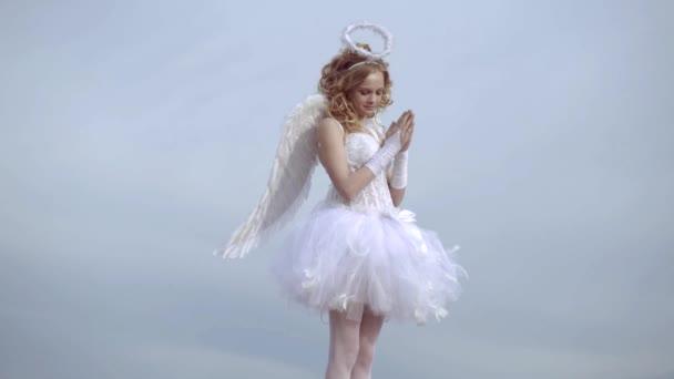 Šťastné děvče z puberty. Dítě s angelickou postavou. Dívka oblečená jako anděl na lehkého nebeském pozadí. Cherub. Sladká andělská holka. Denní karta valentinek.