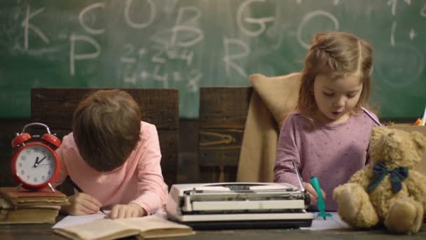 Chlapec a dívka malují na dřevěné židle na pozadí školní tabule. Zpátky do školy. Spolužák vzdělávat a učit se koncept lekce. Děti kreslíte ve třídě.