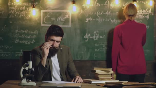 Teacher and student. Back to school. Classmate Educate Friend Knowledge Lesson Concept. Student communicates with the teacher at the board. Bearded teacher with glasses sits at the table with books.