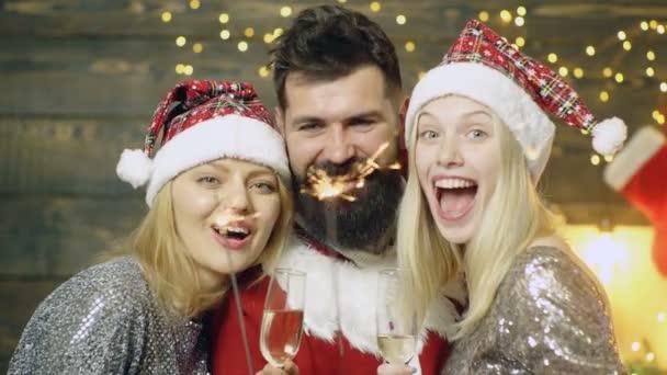 Sexy šťastná skupina přátel z okouzlující party osvětlovací svíčky se baví oslavovat nové roky. Jsou šťastní. Čekám na Santa Klause. Muži a dvě dívky mají předvánoční náladu.