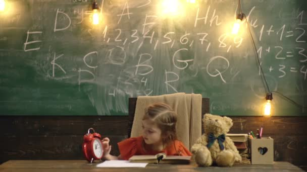 Back to school. Pupil studying at the desk. Child in the class room with blackboard on background. Clock, pencils, books. Kid girl from primary school. Early education. Pupils with school supplies.