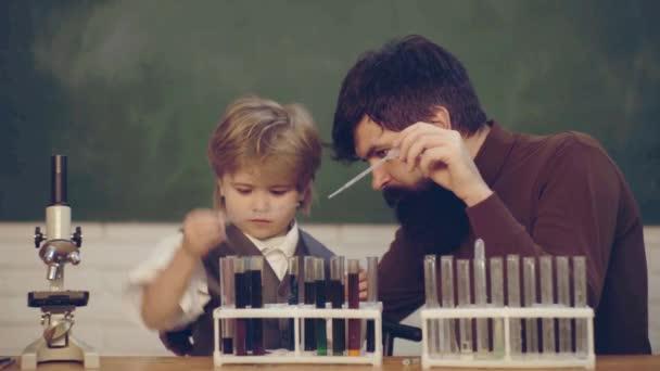 Tanár segítség tanulók tanul az íróasztalok osztályban. Vissza az iskolába, és otthon tanulni. Tanár és gyerek. Első tanítási napon. Fiatal fiú csinál ő iskolai házi feladatát, az apja.