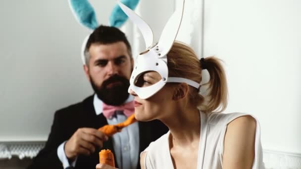 Brutales Paar in Ledermaske, das wie ein Kaninchen an Karotten nagt. Hintergrund. isoliert in weiß. Lustiges Paar. leidenschaftliches Paar in Masken. Zuckerbrot im Mund. bärtiger Mann mit Hasenohren und Zuckerbrot.