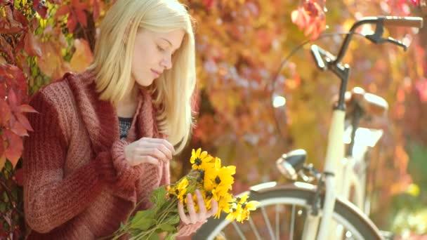 Nő sárga flovers. Nő ősszel ruhát hulló levelek felett természet háttérben. Ősszel és Lombhullás Dreams. Divat lányok szépségápolás.