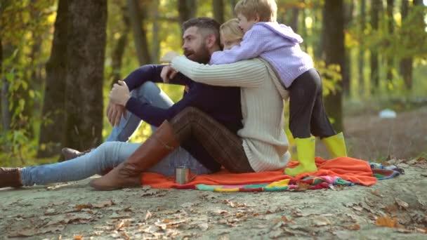 Ritratto di famiglia autunnale colorato. Felici giovani genitori sorridenti con un figlio piccolo che giace nelle foglie dautunno. Giovani genitori e bambini che fanno picnic e si rilassano insieme in una giornata di sole autunnale.