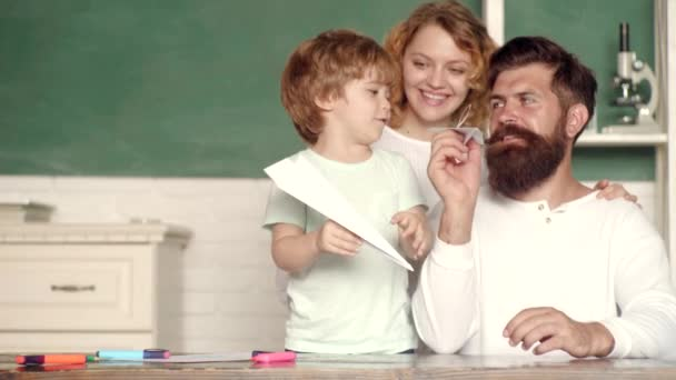Glückliches Kind spielen mit Spielzeugpapier Flugzeug. Kindererziehung und Schülererziehung. Erster Tag in der Schule. Zurück zur Schule. Modelle der Schulgemeinschaft-Partnerschaft.