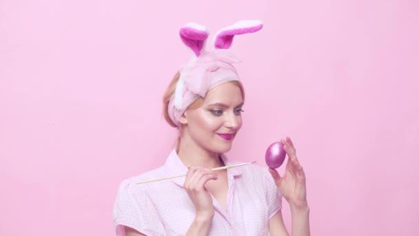 Vicces húsvéti nyuszi festés tojással. Szexi szőke Pinup lány nyuszi füle. Nő nyuszi füle. Szexi PIN fel női modell öltözött jelmezes húsvéti nyuszi. Pin-up stílus.