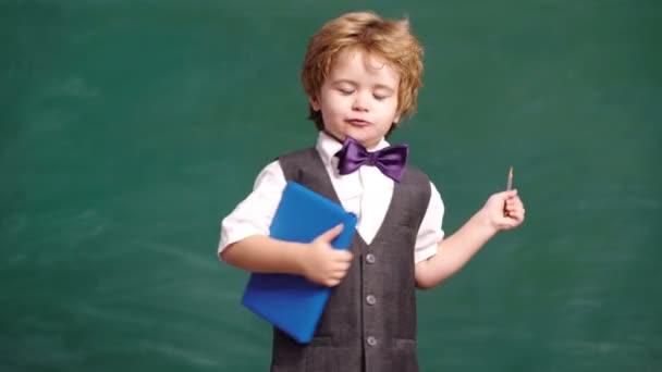 Zpátky do školy. Preschooler poblíž tabule. Chytrý chlapec. Mladý student. Vzdělání a děti. Šťastný učitel. Studenti z lekce. Odstupňování vzdělávání a koncepce lidí. Chytrý kluk.
