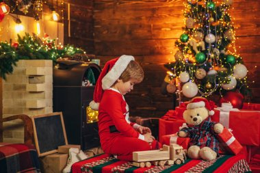 Christmas miracle and new year feelings. A little boy in warm clothes sitting and playing with wooden toys gift. Open-ended Games. First memory of childhood.