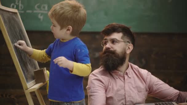 Pupil with teacher at school. Side view father and son learn arithmetic. Daddy explaining equation to cute kid. Pupil teacher at school. Kid pointing at chalkboard while hugging daddy. Background.