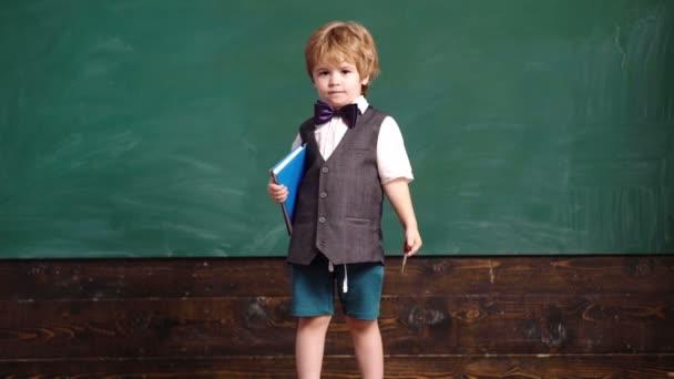 Školní chlapec. Pohledný chlapec na pozadí zelené školní tabule. Zpátky do školy. Zábavný malý školák na vestě na pozadí tabule. Školák s perem a poznámkovým blokem. Koncept učení. Vzdělávání.
