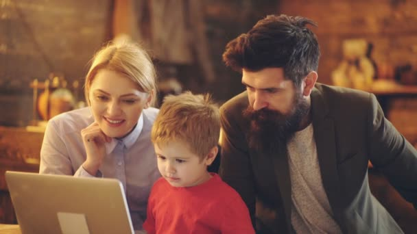 Roztomilá holčička, která se dívá na obrazovku přenosného počítače a dívá se na kreslenečka s rodiči doma. Šťastná máma a malej chlapeček, kteří používají počítač k nakupování internetových nákupů.