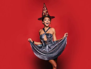Happy gothic young woman in witch halloween costume with hat standing and smiling over red background. Pretty young woman in witch costume. Wide Halloween party art design.
