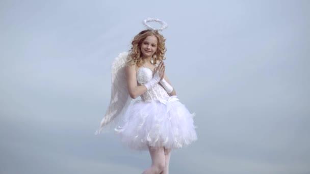 Angel szárnyak baba imádkozni. Szerelmi koncepció. Aranyos tini Cupido a felhő-ég háttérben. Angyal gyermek lány göndör szőke haja-ártatlan lány fogalmát. Imádkozni.