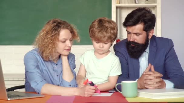 Back to school and home schooling. Cute pupil and his father and mother making schooling work. Happy school kids at lesson in September 1. Family school. Mathematics for kids.