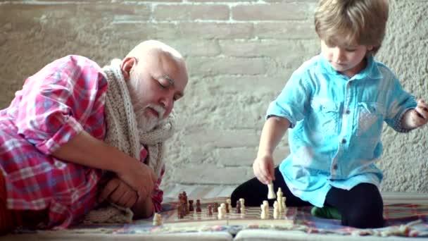 Opa und Enkel spielen Schach, während sie zu Hause Zeit miteinander verbringen. kleiner Junge beim Schachspielen mit seinem Großvater. Reifer Mann mit kleinem Jungen beim Schachspielen.
