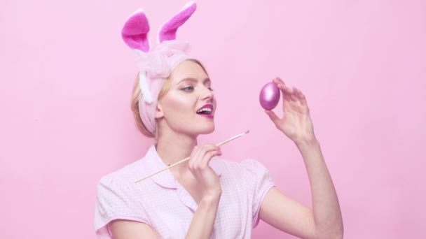 Easter bunny girl painting egg. Sexy beautiful pin up girl with blond hair with bunny ears. Lovely charming pin up girl in bunny ears celebrating Easter.