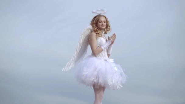 Dívčí anděl se svatozář v bílém andělským obleku. Nádherná dospívající blondýnka s blond kudrnatými vlasy. Milostné přání. Holčička s andělským křídlem a svatozář.