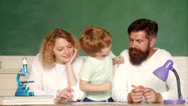 Anya és apa fia együtt iskolázottság. Iskolás gyerekek. Első alkalom az iskolába. Vicces kis gyermek családjával szórakozik a táblára háttérben. Családi iskola. Matematika gyerekeknek.