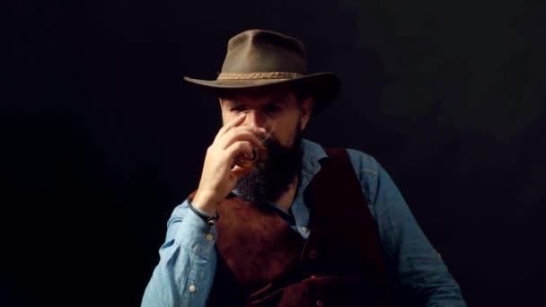 Módní muž v bílé košili a podvazcích. Chlap pije alkohol ze skla. Alkohol Drink. Pití whisky nebo brandy nebo koňaku.
