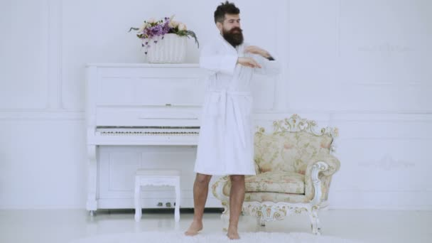 Man cheerful and carefree in bathrobe, having fun, relaxing in luxury hotel in morning, white background. Elite leisure concept. Man with beard and mustache enjoy morning while doing morning exercise.
