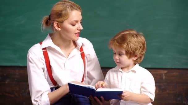 Tanár folytat egy fiatal fiú az iskolai osztályban. Iskolás gyerekek egyenruhában. Tanár az osztályban. Tanár és tanuló. Vissza az iskolába. A fiú és a nő portréja zöld alapon.