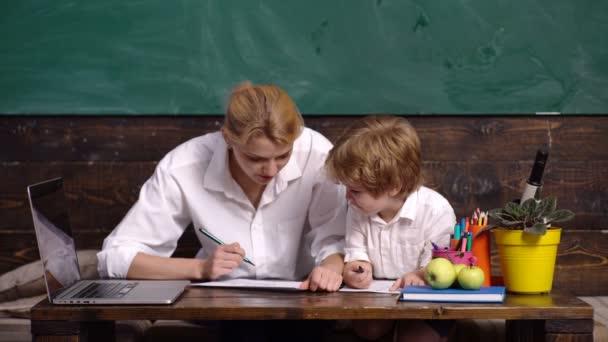 Usmívající se dítě s učitelem. Kluk ve třídě u tabule. Dítě bude připraveno do školy. Den učitelů. Dětský učení ve třídě. Školní koncept. Zpátky do školy. Koncept učení. Učitel a žák.