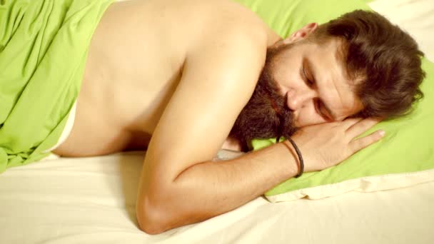 Photo of handsome man sleeping and holding soft green pillow. Handsome man sleeps in the bedroom - lying on bed. Young man is lying on bed and enjoying the morning.