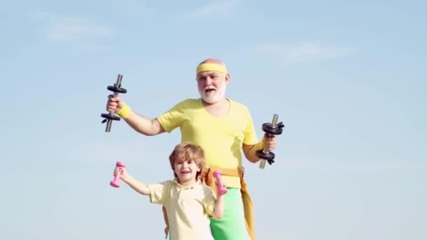 Gesunde Erziehung. Opa und kleiner Enkel üben Hantelübungen im Freien. Sporttrainer und Kind bauen Kraft mit Kurzhanteln auf.