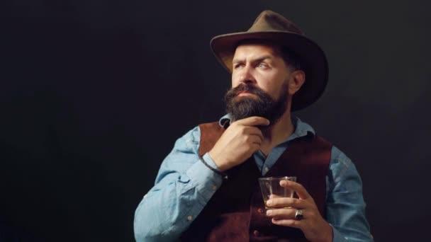 Sommelier íze drága alkoholos ital. Csinos szakállas üzletember iszik drága whisky. Vonzó Bartender a whisky bárban.