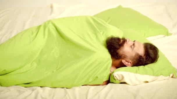 Mladý muž v posteli-snaže se usnout. Mladý muž spí na posteli. Mladý muž leží na posteli a baví se ráno. Tiše spí.