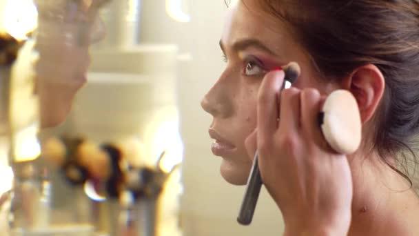 Umělec se aplikuje na skinton. Kosmetický a módní make-up. Nádherná ženská make-up.