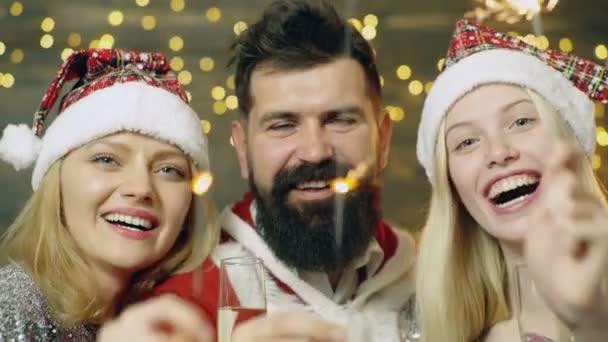 Mann und zwei Frauen in Weihnachtskostümen zünden Wunderkerzen an, Nahaufnahme. Lichterketten. Frohe Weihnachten. Freunde feiern Weihnachten oder Silvesterparty mit Bengalischen Lichtern. verschwommenes Licht Hintergrund.