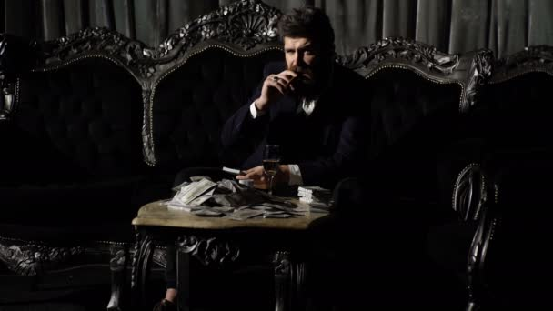 Millionaire smokes and drinks on luxurious sofa. Bearded man with confident face and money. Businessman with long beard has cigar, champagne and dollars. Luxury lifestyle, fashion and success concept.
