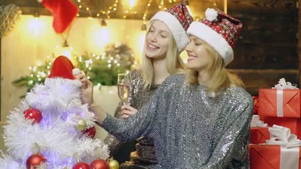 Veselé Vánoce a šťastný nový rok. Dvě blonďaté dívky a vánoční dekorace. Přítelkyně oslavující nové roky párty popíjení šampaňského nový rok. Šťastné lidi. Opravdové emoce.