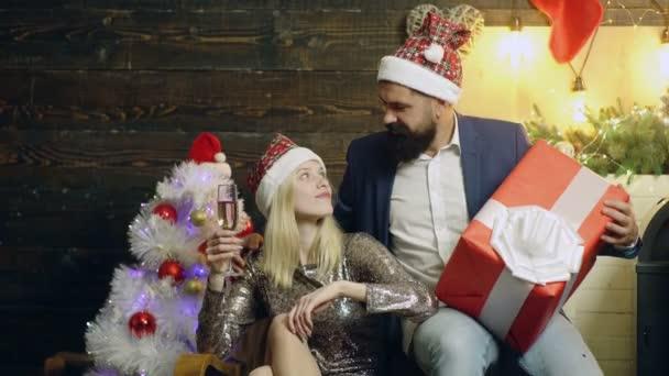 Mann macht seiner Freundin ein Weihnachtsgeschenk. Frohe Weihnachten und ein gutes neues Jahr. Paar mit Weihnachtsgeschenk. Neujahrsgeschenk. Konzept von: Geschenk, Liebe, Valentinstag, Weihnachten, Neujahr.