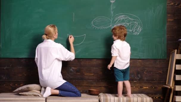 Erzieherin und Kind malen Bild auf Kreidetafel. Frau und Junge zeichnen. Mutter und Sohn malen mit Kreide an der Schultafel. Schöner Kleinkind-Junge zeichnet auf Kreidetafel auf Holzgrund.