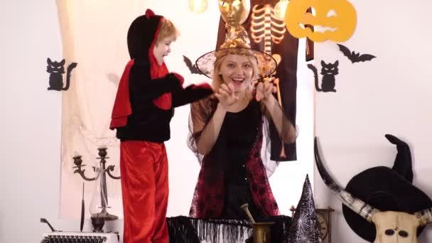 Anya és fia boszorkány jelmezek és boszorkánykalapok. Halloween sütőtök fej Jack lámpa égő gyertyákkal. Titkai Magic boldog halloween. Halloween ünnepség fogalmát. Halloween anya és fia