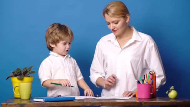 Mom and child spend time together. Family happiness concept. Mother teach son on blue background. Woman and little boy. Mother and son drawing together, mom helping with homework on blue background.