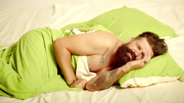 Man bearded hipster having problems with sleep. Sleep. Man sleep on bed with very deep sleep. Photo of handsome man sleeping and holding soft green pillow.