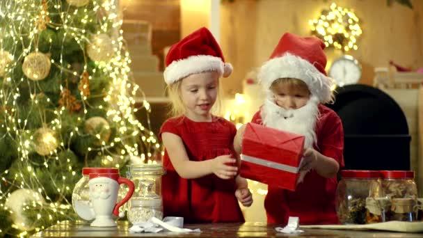 fröhliche süße Kinder beim Öffnen eines Weihnachtsgeschenks. zwei glückliche Kinder Tochter und Sohn oder Schwester und Bruder mit Weihnachtsgeschenk. glückliches Kind hat Spaß mit Geschenk.