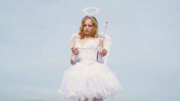 Andělská holčička s bílými křídly. Bůh Lásky. Hezká puberťačka. Šíp lásky. Dívka anděl s svatozáří v bílých andělských šatech. Portrét malé Amorské holčičky. Teen angel. Koncept lásky
