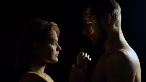 Erotický koncept. Erotika s párem mají zlatý make-up a dotýkají se navzájem. Pár pohledů a držení se za ruce na černém pozadí. Halloweenská oslava. Světelné kartáče. Zlato.