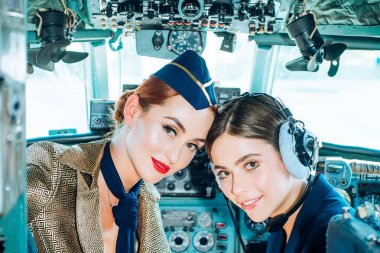 Portrait of two smiling women pilots. Beautiful Smiling Young Woman Pilot Sitting in Cabin of Modern Aircraft. Stewardess and Flight Instructor in an Aircraft Cockpit. Pilot and Stewardess.