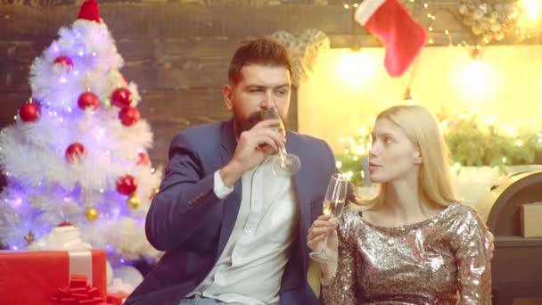 Porträt zweier Menschen auf der Silvesterparty. Paar mit Gläsern Champagner. Porträt eines süßen Paares, das einander anstarrt.