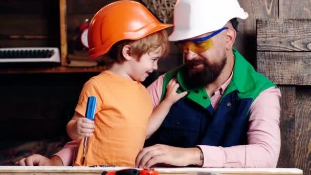 Koncept truhlářství a práce s lidmi - otec a syn s kladivem zatloukající hřebík do dřevěné desky v dílně. Koncept předškolního vzdělávání.