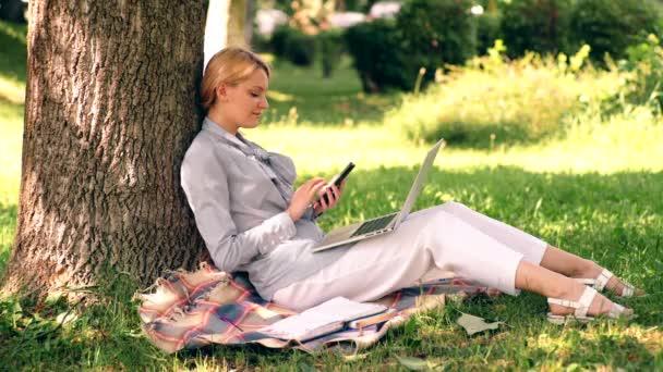 Mladá žena sedí v parku na zelené trávě s notebookem a smartphonem, studentka studuje venku.