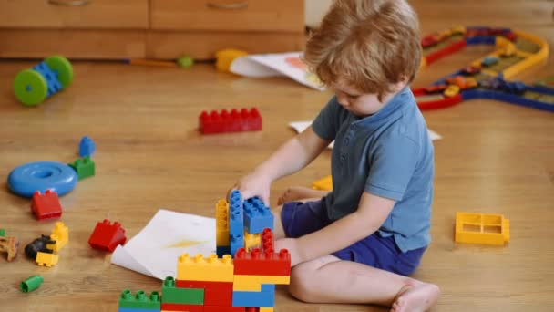 Funny curly baby boy with educational toy blocks. Children play at day care or preschool. Mess in kids room. Toddlers build a tower in kindergarten. Child playing with colorful toys
