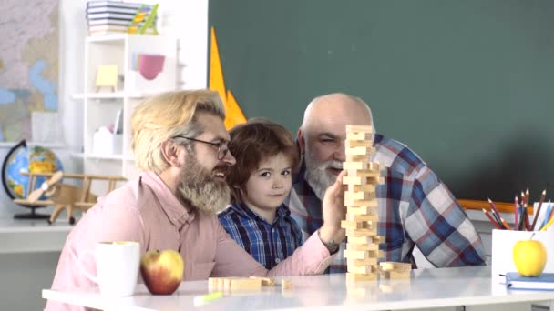 Three generations of men having fun together. Grandfather, father teaching grandson how to play games. Family tree. Excited teach. Different mans ages. Happy mature teachers.